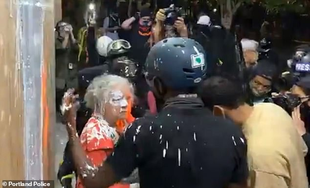 More demonstrations took place across the city and police shut down the streets surrounding a precinct overnight on Thursday. Police said this woman had paint thrown over her by protesters as she tried to stand guard outside a police precinct