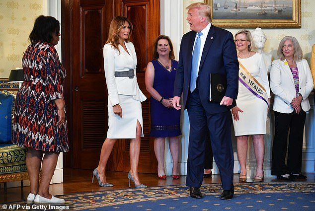 President Donald Trump and First Lady Melania Trump arrive for the signing ceremony of a proclamation on the 100th anniversary of the ratification of the 19th Amendment during an event in the Blue Room of the White House in Washington Tuesday