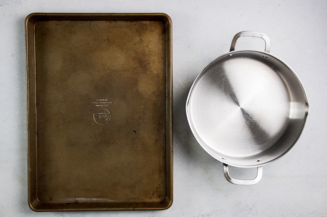 overhead photo of a baking sheet next to a stainless steel pot