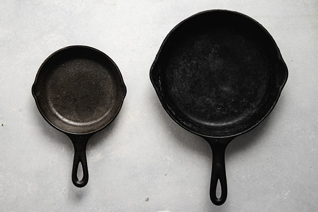 overhead photo of a large cast iron skillet next to a small cast iron skillet