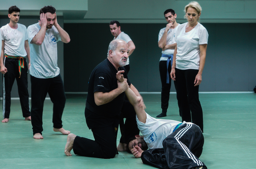 Avi Attlan, kneeling, teaching Krav Maga to students in Saint Mande, March 23, 2017. (Cnaan Liphshiz/JTA)